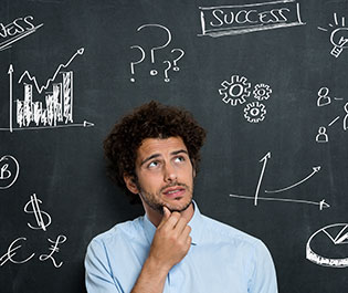 /man thinking in front of a blackboard